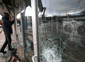 DELLWOOD, MO – NOVEMBER 25: A reporter looks through the window of a laundromat that was damaged during a demonstration on November 25, 2014 in Dellwood, Missouri. Demonstrators caused extensive damage in Ferguson and surrounding areas last night after a St. Louis County grand jury decided to not indict Ferguson police Officer Darren Wilson in the shooting of Michael Brown. (Photo by Justin Sullivan/Getty Images)